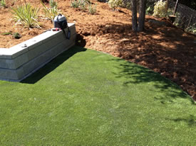 AFTER the beautiful seamless artificial grass installation butted up against a retaining wall.