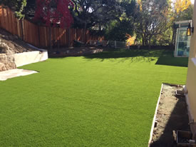 The complete project showng the beautiful seamless artificial grass and fence and home in background.