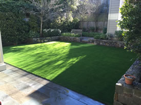 AFTER the beautiful synthetic grass installation around a Moss Rock Retaining Wall.